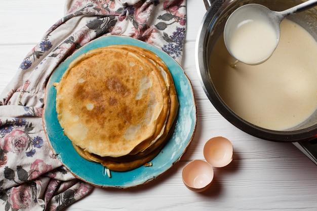 Der prozess der herstellung traditioneller dünner pfannkuchen. pfannkuchen und eine schüssel mit einem test auf dem tisch.