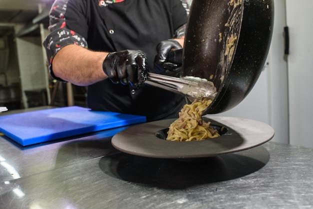 Der prozess der herstellung von carbonara-nudeln für restaurantgäste. leckeres essen.
