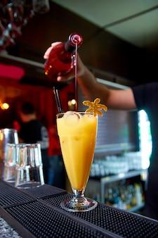 Der prozess der herstellung von cocktail an der bar im nachtclub.