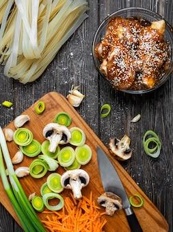 Der prozess der herstellung von hühnernudeln mit teriyaki-sauce und sesam