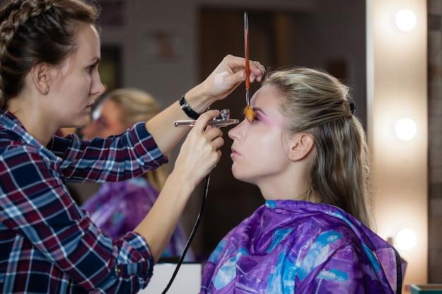 Der prozess der herstellung von modernem make-up mit airbrush. visagistin kreiert und konzentriert