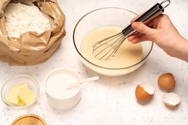 Der prozess der herstellung von pfannkuchenteig mit zutaten auf einem leuchttisch, eiern und mehl wird mit einem mixer geschlagen.