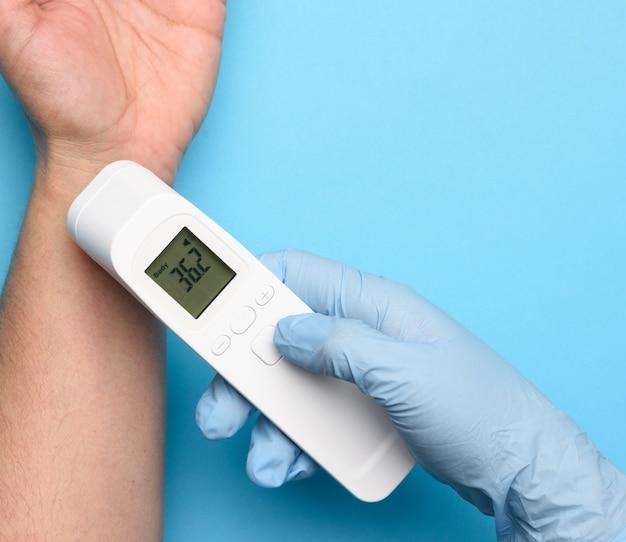 Der prozess der messung der körpertemperatur am handgelenk mit einem berührungslosen thermometer, nahaufnahme