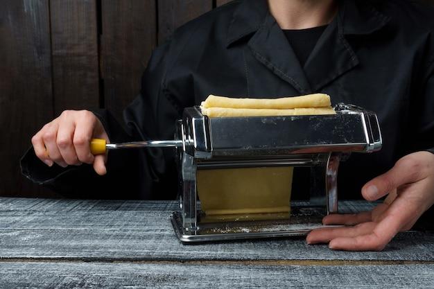 Der prozess der zubereitung frischer nudeln. koch bereitet nudelteig auf einer schreibmaschine zu, textfreiraum