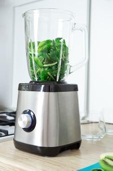 Der prozess der zubereitung von grünem smoothie in einem küchenmixer. kochen von vitamin-grün-smoothie. das konzept einer gesunden ernährung, entgiftung, gesunde lebensweise, vegetarismus, ernährung.