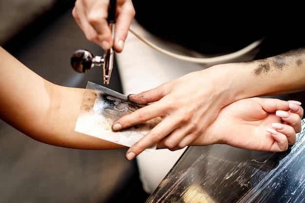 Der prozess des anbringens eines temporären tattoos.