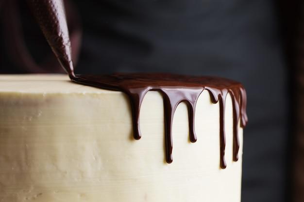 Der prozess des dekorierens des kuchens mit flüssiger schokolade