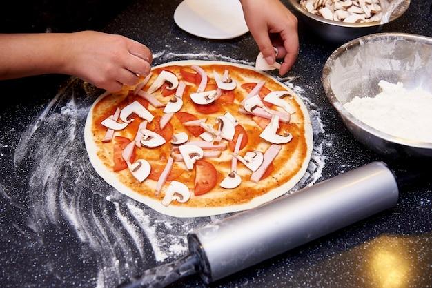 Der prozess des kochens der pizza mit fleisch, pilzen, tomaten und käse.