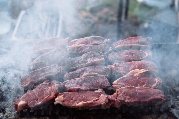 Der prozess des kochens von steakstücken auf dem grill. stücke gegrilltes und rohes fleisch.