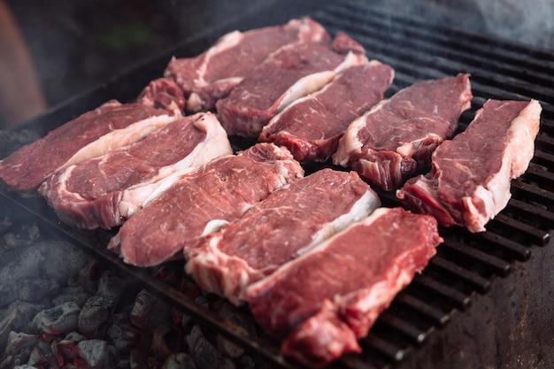 Der prozess des kochens von steakstücken auf dem grill