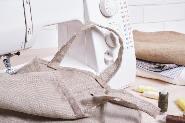 Der prozess des nähens von öko-taschen mit einer nähmaschine, näherin arbeitsplatz natürliche stoffe, fäden, schere, umweltfreundliche lifestyle-konzept trendfarben
