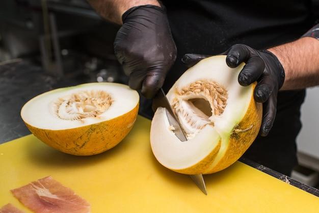 Der prozess des schneidens einer köstlichen und gesunden reifen melone