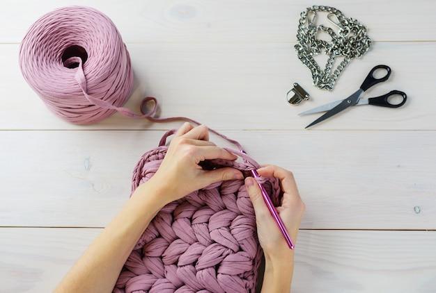 Der prozess des strickens von gestrickten threads auf einem holztisch.