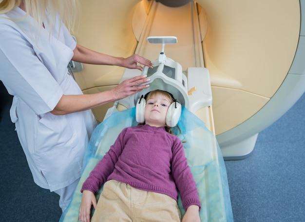Der radiologe bereitet das kleine mädchen auf eine mrt-gehirnuntersuchung vor