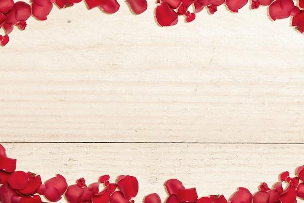 Der rahmen der roten rosenblätter mit einem hölzernen tischhintergrund