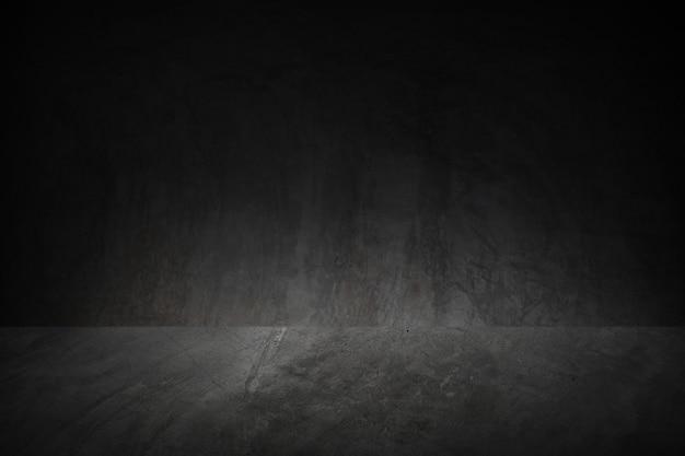Der raum hat eine dunkle loft-zementwand für die inneneinrichtung oder produktpräsentation