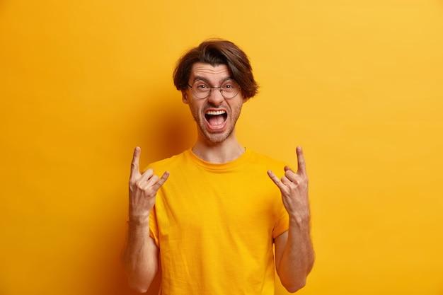 Der rebellische unrasierte hipster-typ lässt rockgeste laut schreien und ist teil einer konzertband, trägt runde brille und lässiges t-shirt isoliert über gelber wand körpersprachkonzept language