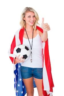 Der recht blonde fußballfan, der usa trägt, kennzeichnen die flagge, die sich daumen zeigt