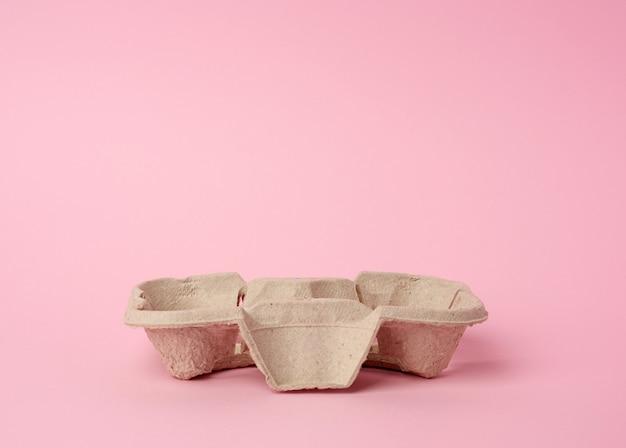 Der recycling-ständer aus pappe für heiße getränke für zwei tassen befindet sich auf einem rosa platz