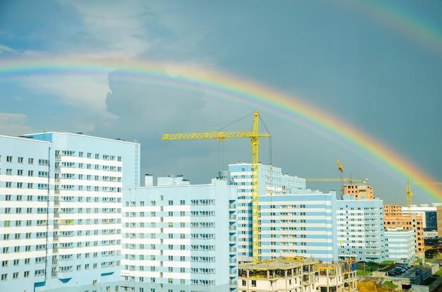 Der regenbogen erstreckt sich über die hochhäuser der stadt
