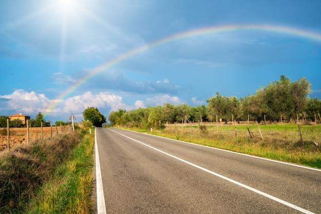 Der regenbogen über straße und landwirtschaftslandschaft.