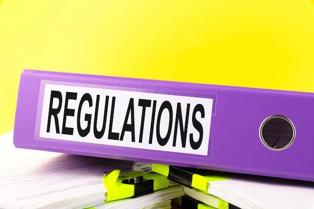 Der reglementstext wird auf einem bürostapel mit einem gelben papierstapel in einen büroordner geschrieben