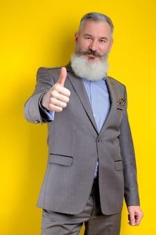 Der reife bärtige geschäftsmann des studio-porträts, gekleidet in den grauen anzug, zeigt daumen hoch