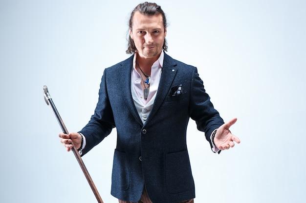 Der reife bärtige mann in einem anzug, der stock hält. isoliert auf einem blauen studio.