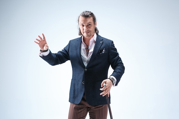 Der reife bärtige mann in einem anzug, der stock hält. isoliert auf einem blauen studiohintergrund.
