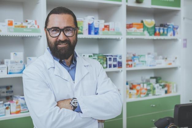Der reife bärtige phrmacist, der an arbeitet, ist drogerie