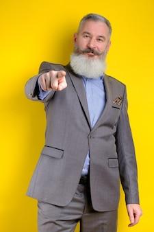 Der reife geschäftsmann des studio-porträts, gekleidet in den grauen anzug, zeigt auf kamera, ich wähle sie konzept, gelber hintergrund