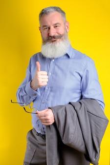 Der reife geschäftsmann des studio-porträts, gekleidet in den grauen anzug, zeigt daumen hoch, erfolgreiches geschäftskonzept, gelber hintergrund