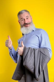 Der reife geschäftsmann des studioporträts, gekleidet im grauen anzug, zeigt daumen hoch, erfolgreiches geschäftskonzept, gelber hintergrund