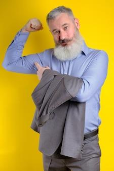 Der reife geschäftsmann des studioporträts, gekleidet im grauen anzug, zeigt seinen aufgepumpten bizeps, starkes geschäft, das im unternehmertumkonzept ausübt.