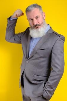 Der reife geschäftsmann des studioporträts im grauen anzug zeigt seinen aufgepumpten bizeps