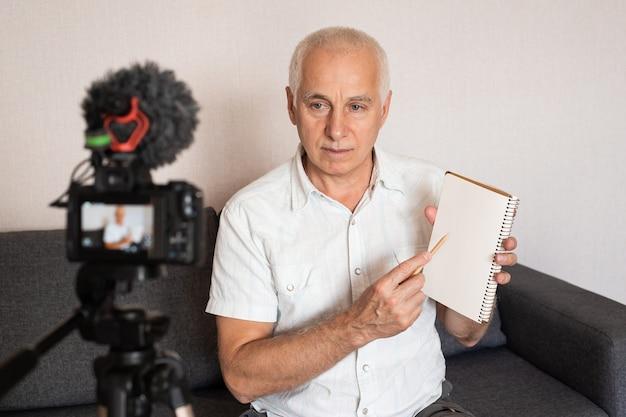 Der reife, grau hörbare professor zeigt etwas, das ein video für eine vorlesung zu hause mit einer videokamera und online-bildung macht