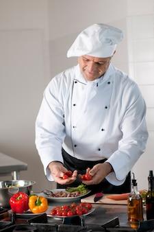 Der reife küchenchef wählt sorgfältig kirschtomaten für die zubereitung des abendessens im restaurant aus