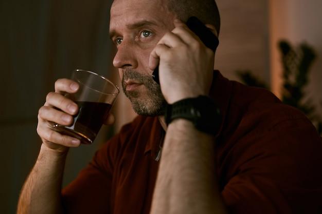 Der reife mann hat ein gespräch auf dem handy und trinkt alkohol, während er zu hause sitzt