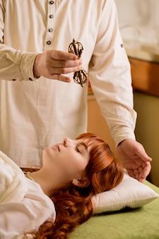 Der reiki-meister arbeitet mit einem patienten mit einem vajra