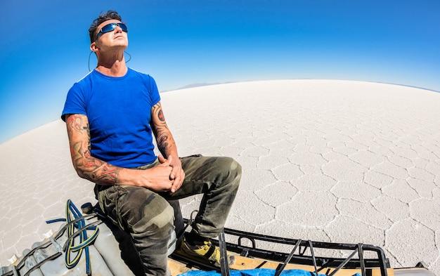 Der reisende des jungen mannes, der entspannt, machen pause an saltflats salar de uyuni in der südamerikanischen bolivianischen wüste