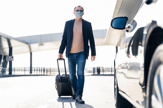 Der reisende mann zieht den koffer, kehrt vom flughafen zurück, nähert sich dem auto und trägt eine medizinische maske