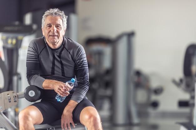 Der rentner hält sich beim training im fitnessstudio fit und ruht sich mit einer flasche wasser aus.