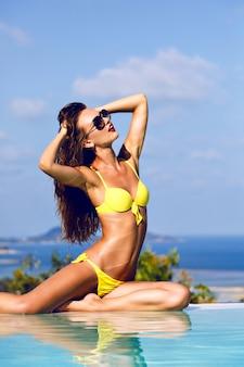 Der rest der insel in der nähe des pools. outdoor-mode der schönen, eleganten, sexy frau mit perfekt gebräuntem körper, in der sonne liegend und genießen sie ihren urlaub. tragen sie einen hellen, stilvollen bikini und eine sonnenbrille.