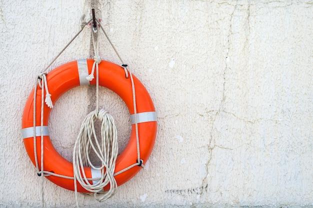 Der rettungsring mit schnur wird an einer betonwand in der nähe des strandes aufgehängt