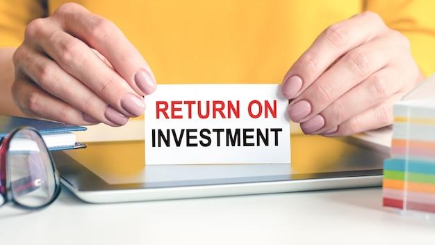 Der return on investment wird auf eine weiße karte in den händen einer frau geschrieben