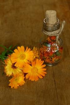 Der ringelblumenextrakt. heilpflanzen. flaschen und getrocknete calendula officinalis blütenblätter mit mazeriertem öl auf holztisch.