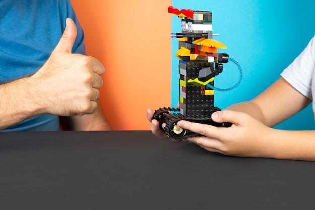 Der roboter wird vom designer zusammengebaut. kurse in robotik. mint-ausbildung. die wissenschaft. technologie. technische mathematik
