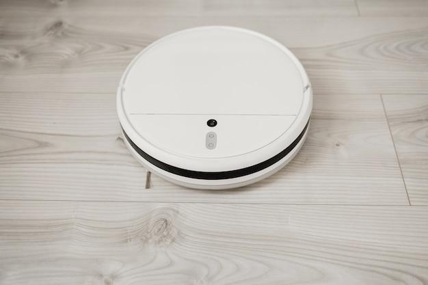 Der roboterstaubsauger führt eine automatische reinigung des laminats der wohnung durch. intelligentes zuhause.