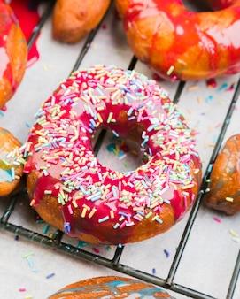 Der rosa gefrorene donut, der herein bedeckt wird, besprüht auf metallischem behälter