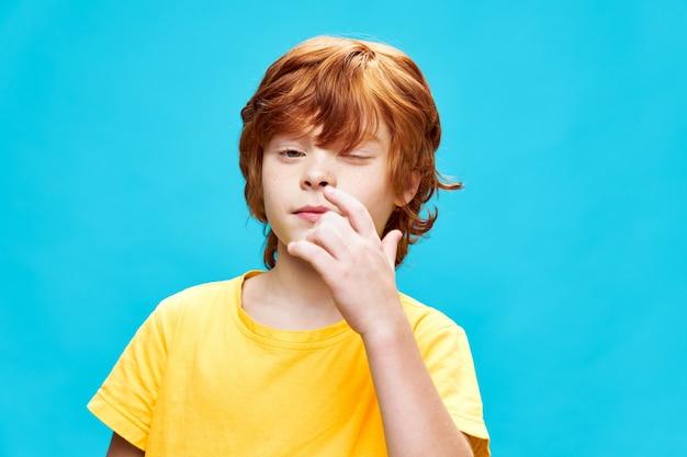 Der rothaarige junge mit geschlossenem auge hält den handfinger nahe dem gelben t-shirt-blauen hintergrundlebensstil der nase